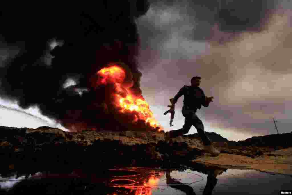 Api dan asam membumbung dari sumur-sumur minyak yang dibakar oleh kaum militan Islamic State sebelu mereka meninggalkan kawasan produsen minyak di Qayyara, Irak.