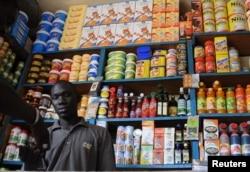 FILE - A shopkeeper receives payment in a roadside kiosk in Senegal's capital Dakar.