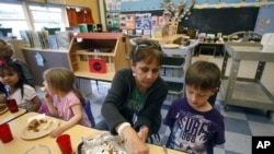 Teacher Diana Feke helps Mason Baker during lunch at the Eastham Community Center Claskamas County Children's Commission Head Start, April 9, 2012, in Oregon City.