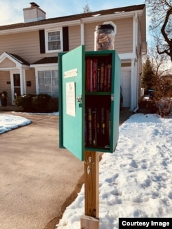 Toples berisi biskuit anjing diletakkan di atas Little Free Library di Mount Prospect, Illinois. (Courtesy: Alfred Ticoalu)