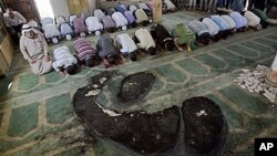 Palestinians pray inside a partially burned mosque in the West Bank village of Beit Fajjar, near Bethlehem, 04 Oct 2010