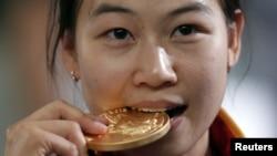 La tiradora Yi Siling muerde su medalla dorada, la primera otorgada en estos Juegos, en las barracas de la Real Artillería, en Woolwich, Londres.