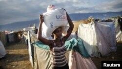 Seorang perempuan di Cite Soleil, Port-au-Prince di Haiti, memanggul karung berisi beras yang dibagikan lembaga bantuan AS, USAID. (Foto: Dok)