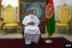 FILE - Afghan warlord and former mujahideen leader Ismail Khan looks on during an interview at his residence in Herat province, May 29, 2015.