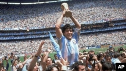 In this June 29, 1986 file photo, Diego Maradona holds up his team's trophy after Argentina's 3-2 victory over West Germany at the World Cup final soccer match at Atzeca Stadium in Mexico City. (AP)