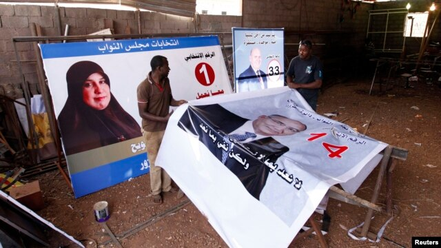 Workers prepare election campaign posters for Libya's House of Representatives in Tripoli, June 18, 2014