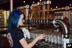 Maya Martinez, a manager at the Rio Bravo Brewing Company in Albuquerque, N.M., pours a craft beer, May 3, 2017, just days before the brewery was set to unveil a new beer on Cinco de Mayo.
