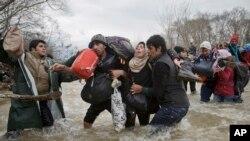 Deux hommes soutiennent une femme en traversant une rivière, tentant d'atteindre la Macédoine, 14 mars 2016.