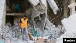 Trabajadores de ayuda de la Media Luna Roja inspeccionan suministros médicos tras el bombardeo a un depósito médico el 30 de abril de 2016 en Alepo, Siria.