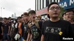 Para mahasiswa meneriakkan slogan di luar Lapangan Golden Bauhinia, tempat diselenggarakannya upacara pengibaran bendera untuk memperingati Hari Nasional CHina di Hong Kong (1/10).