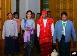 FILE - Myanmar opposition leader Aung San Suu Kyi, second from left, walks with members of her National League for Democracy party upon their arrival to attend regular session of the parliament's Lower House in Naypyitaw, Myanmar, Dec 1, 2015.