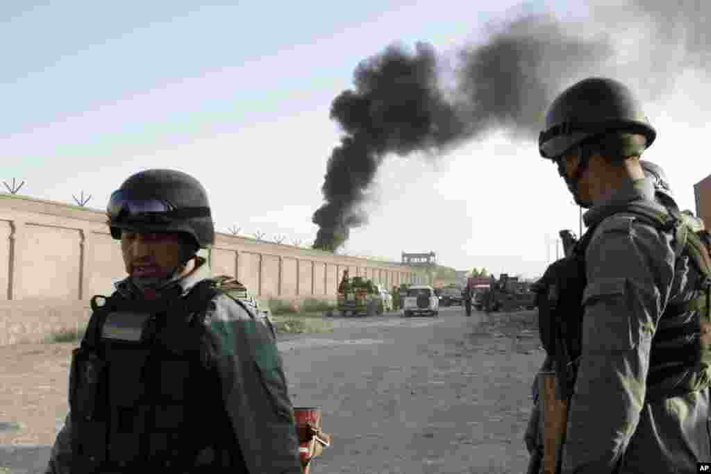 Afghan security force members stand guard near the entrance gate to a NATO compound following a suicide bombing in Kabul, July 2, 2013.