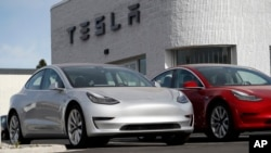 FILE - New 2018 Model 3 vehicles are seen on a Tesla dealer's lot in Littleton, Colorado, April 15, 2018.