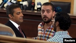 Al Jazeera television journalists Mohamed Fahmy, left, and Baher Mohamed, second from left, talk before hearing the verdict at a court in Cairo, Egypt, Aug. 29, 2015.