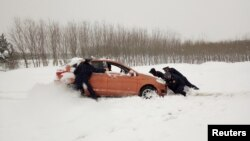 Law enforcement officials of highway management help push a car in snow in Xiangyang, Hubei province, China Jan. 4, 2018.