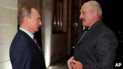 FILE - Russian President Vladimir Putin, left, and Belarusian President Alexander Lukashenko meet in the Bocharov Ruchei residence in the Black Sea resort of Sochi, Russia, Sept. 15, 2015.
