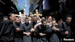 Fieles cristianos se toman de los brazos durante la procesión del Viernes Santo en la Via Dolorosa en Jerusalén.