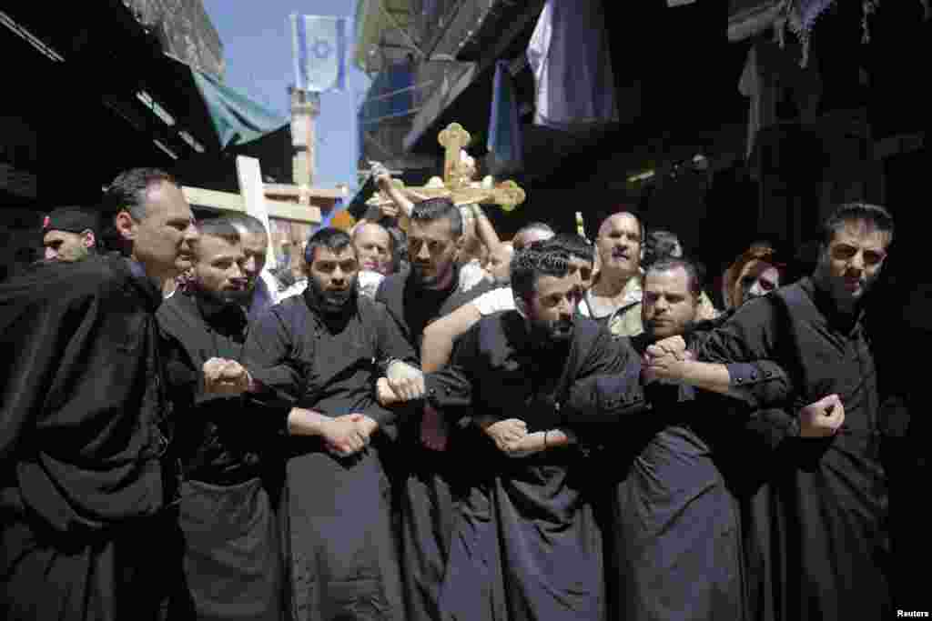 Christian worshippers lock arms during a procession along the Via Dolorosa on Good Friday during Holy Week in Jerusalem's Old City, April 18, 2014.