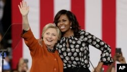 Democratic presidential candidate Hillary Clinton, accompanied by first lady Michelle Obama, greet supporters during a campaign rally in Winston-Salem, N.C., Oct. 27, 2016. Researcher Susan Madsen says there are striking similarities among powerful women across the globe.