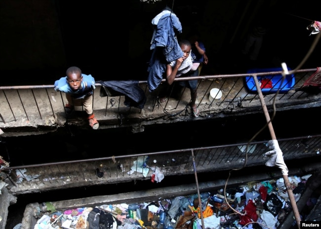 FILE - Children stand amid trash in a building earmarked for demolition in the Mathare neighborhood of Nairobi, Kenya, May 17, 2016.