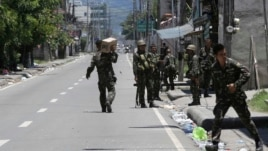 Government troopers patrol their area as fighting continues for the sixth day between the military and Muslim rebels, Sept. 14, 2013 at Zamboanga city in southern Philippines.