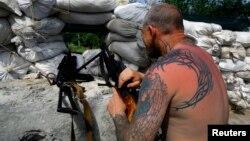 Dân quân thân Nga canh gác tại một chốt kiểm soát trong khu vực ngoại ô của thị trấn phía đông Slaviansk ở Ukraina, ngày 19/5/2014.