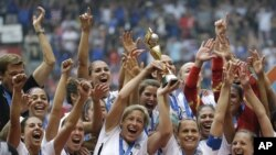 FILE - In this July 5, 2015, file photo, the United States Women's National Team celebrates with the trophy after they beat Japan 5-2 in the FIFA Women's World Cup soccer championship in Vancouver, British Columbia, Canada.
