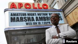 "FILE - Historian Billy Mitchell poses outside the Apollo Theater in the Harlem section of New York, June 11, 2014. Attempts to rename a Harlem neighborhood ""SoHa"" have enraged longtime residents."