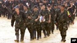 """El comandante guerrillero conocido como """"Grannobles"""" (derecha), acompaña a algunos de los 242 policías y soldados que fueron capturados por la guerrilla de las FARC en la población colombiana de La Macarena."""
