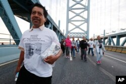 Alvaro Bautista, of Camden, N.J., crosses the Benjamin Franklin Bridge to later hear Pope Francis celebrate Sunday Mass in Philadelphia, Sept. 27, 2015.