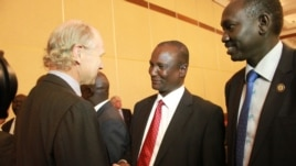 Taban Deng Gai (center), chief negotiator from South Sudan's opposition at peace talks in Addis Ababa, shakes hands with an unidentified observer.