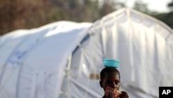 利比里亚难民营里一位科特迪瓦女孩拿着利比里亚货币去购买食物(2011年5月25号资料照)。