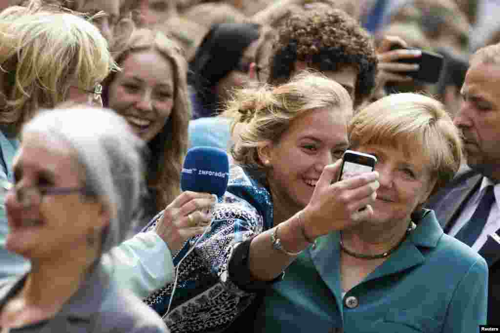 German Chancellor Angela Merkel (R) has her picture taken with a pupil as she arrives for a visit to the Heinz Schliemann grammar school in Berlin.