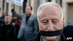 FILE - A demonstrator with his mouth covered stands outside the Istanbul courthouse, where Turkish opposition Cumhuriyet daily's editor-in-chief Can Dundar and Ankara bureau chief Erdem Gul attend their trial, April 1, 2016.