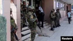 Soldiers of the Jamaica Defense Force (JDF) stand guard outside the Electoral Office of Jamaica in Kingston, Feb. 29, 2016.