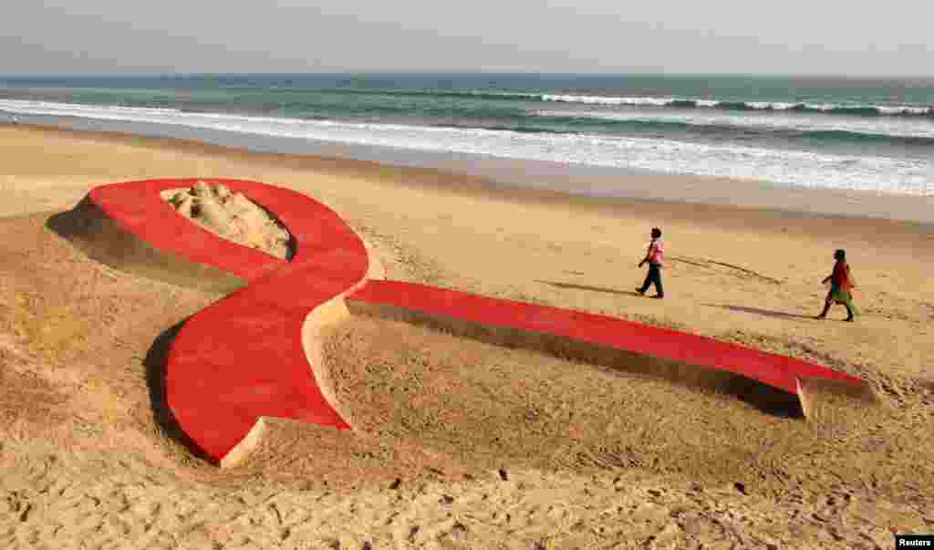 People walk near a red ribbon sand sculpture created by Indian sand artist Sudarshan Patnaik on a beach in the eastern Indian state of Odisha, November 30, 2012.