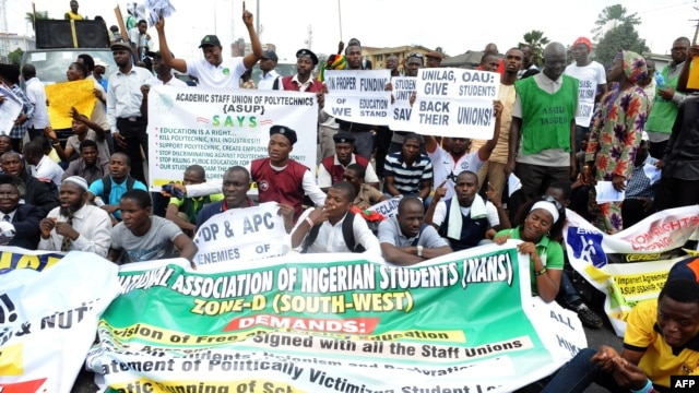 FILE - Students and workers carry placards as they sit on the Lagos-Ikorodu highway to protest against the suspension of academic activities following a nationwide strike by lecturers in state-owned universities, Aug. 13, 2013 in Lagos.