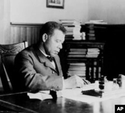 Tuskegee Institute President Booker T. Washington works at his desk in a photo taken around 1905.