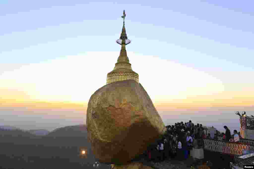 Buddhist devotees wait to offer gold to the Kyaikhtiyo Pagoda, also known as the Golden Rock Pagoda, in Mon State, Burma, photo made available Feb. 10, 2014.