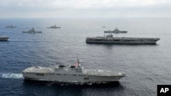 In this photo taken Nov. 16, 2012 and released by U.S. Navy, the USS George Washington aircraft carrier, second row from bottom right, and JS Hyuga, bottom, cruise with other ships from the U.S. Navy and the Japan Maritime Self-Defense Force in East China Sea.