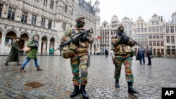 FILE - Belgium police officers patrol the Grand Place in central Brussels, Belgium, Nov. 24, 2015.