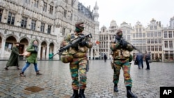 Belgium police officers patrol the Grand Place in central Brussels, Nov. 24, 2015.