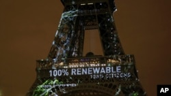 FILE - Artwork entitled 'One Heart One Tree' by artist Naziha Mestaoui is displayed on the Eiffel tower ahead of the 2015 Paris Climate Conference, in Paris. The Paris Agreement on climate change came into force Nov. 4, 2016.