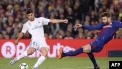 Marco Asensio, le milieu de terrain du Real Madrid, rivalise avec le défenseur espagnol de Barcelone, Gerard Pique au stade Camp Nou de Barcelone, le 6 mai 2018.