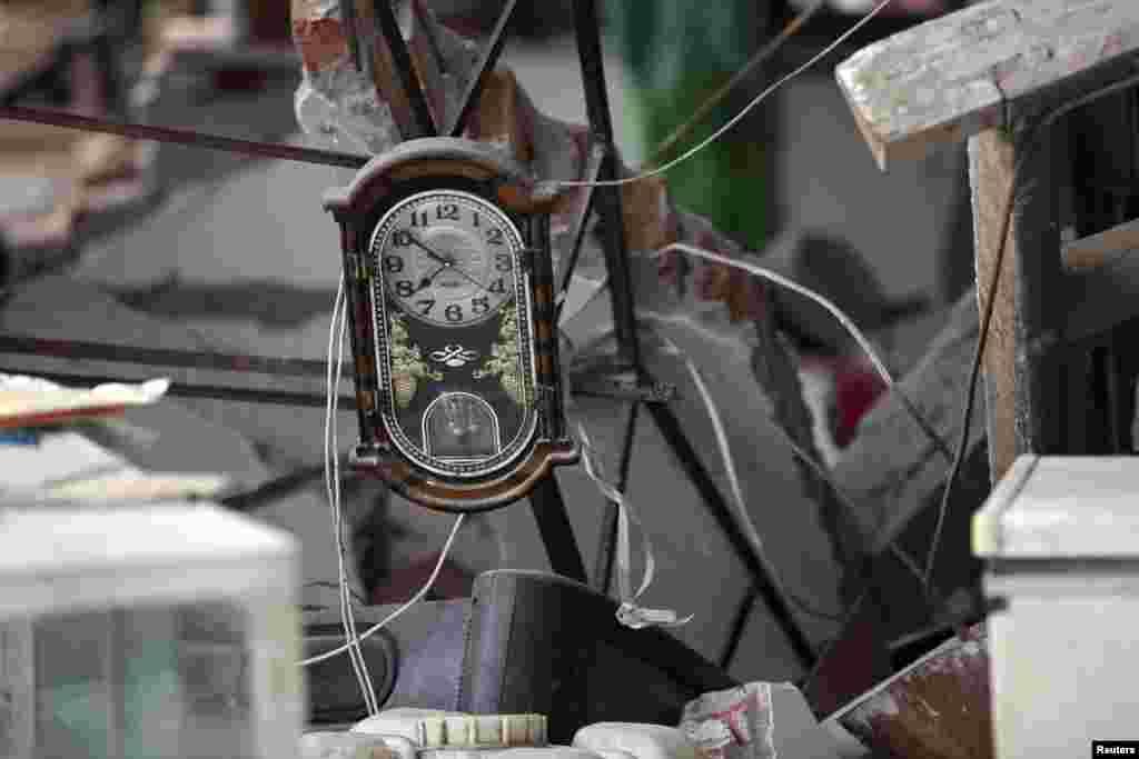 Một cái đồng hồ nằm giữa đống đổ nát của một ngôi nhà bị sập sau trận động đất mạnh 6,6 độ Richter, tại làng Long Môn, huyện Lộ Sơn, tỉnh Tứ Xuyên, ngày 20 tháng 4, 2013.