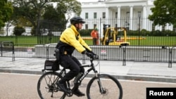 FILE - A member of the U.S. Secret Service patrols on bicycle in front of the North Lawn of the White House in Washington, Oct. 23, 2014.