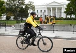 Arhiva - Pripadnike Tajne službe SAD patrolira na biciklu ispred severnog travnjaka Bele kuće u Vašingtonu, 23. oktobra 2014.