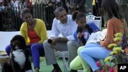 El presidente Barack Obama, Michelle Obama, y la mascota familiar, Bo, escuchan a las hijas de la pareja presidencial Sasha y Malia.