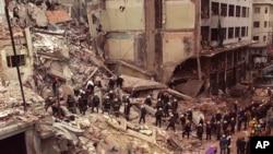 Lính cứu hỏa và nhân viên cứu hộ tìm kiếm trong đống đổ nát của trung tâm cộng đồng của người Do Thái sau vụ đánh bom hồi năm 1994.