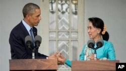 Presiden AS Barack Obama (kiri) dan pemimpin oposisi Myanmar Aung San Suu Kyi berjabatan tangan dalam konferensi pers di rumahnya di Yangon, Myanmar (14/11). (AP/Pablo Martinez Monsivais)
